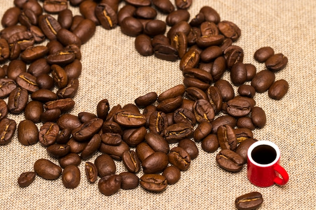 Herz aus kaffeebohnen und eine tasse auf sackleinen