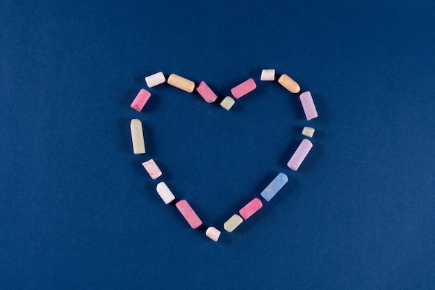 Herz aus kreidepastellfarben auf trendigem klassischem blauem 2020-farbhintergrund. valentinstag 14. februar konzept. flache lage, kopienraum, draufsicht, banner.