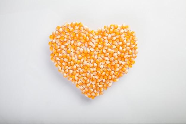 Herz aus mais auf weißer wand, gesundes leben und ernährungskonzept