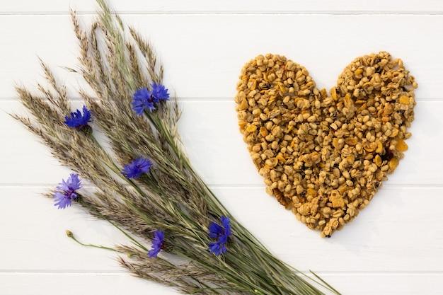 Herz aus müsli, ährchen und kornblumen auf einem weißen hölzernen hintergrund gelegt. flach liegen. speicherplatz kopieren.