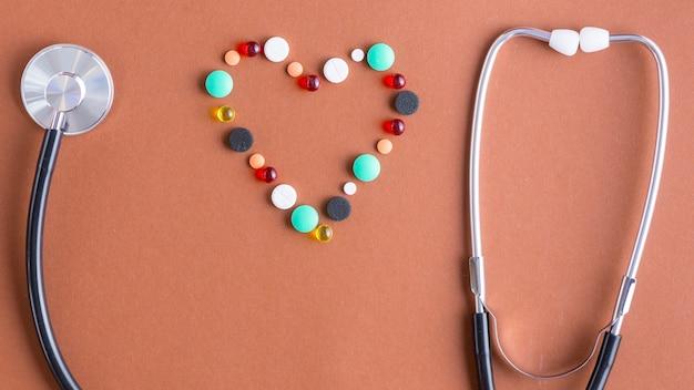 Herz aus pillen in der nähe von resonator und ohrstöpsel des stethoskops