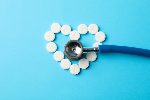 Herz aus pillen und stethoskop auf blauem hintergrund, platz für text