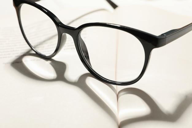 Herz aus schatten und brille auf geöffnetem buch, nahaufnahme