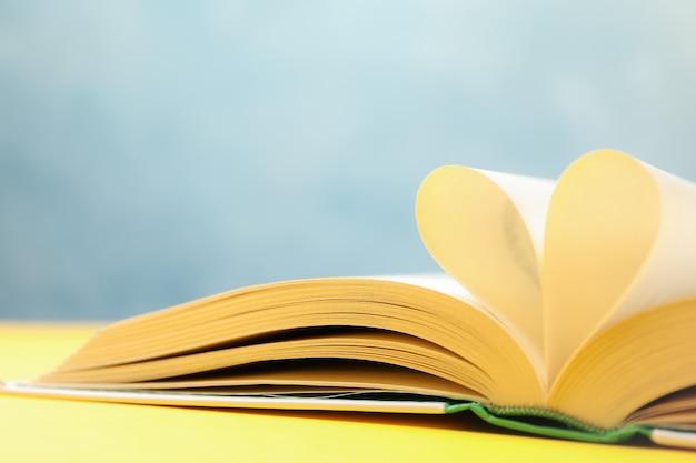 Herz aus seiten. buch auf gelbem tisch, platz für text