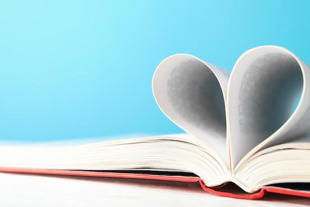 Herz aus seiten. buch gegen blauen raum, platz für text