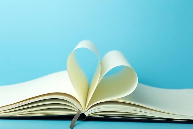 Herz aus weißen seiten des notizblocks auf einem blauen desktop-hintergrund.