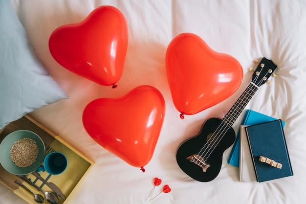 Herz ballons und ukulele auf dem bett