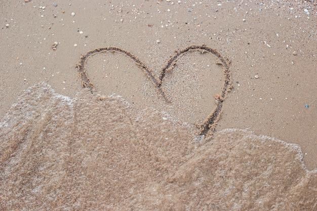 Herz, das an einem sandigen strand gezeichnet wird, wäscht eine welle ab.