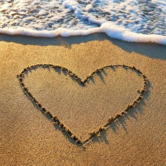Herz, das auf den strandsand mit meerschaum und welle gezeichnet worden war