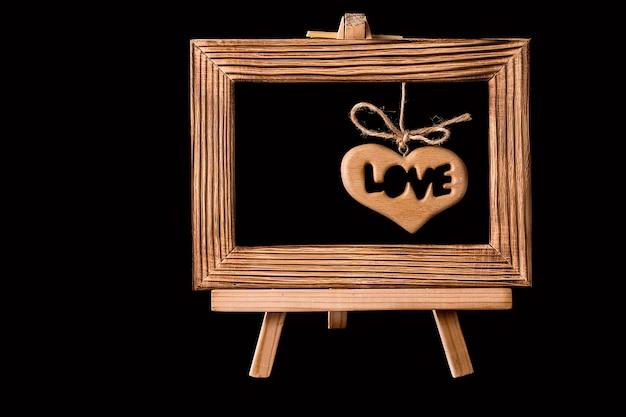 Herz, das im alten bilderrahmen auf schwarzem hängt.
