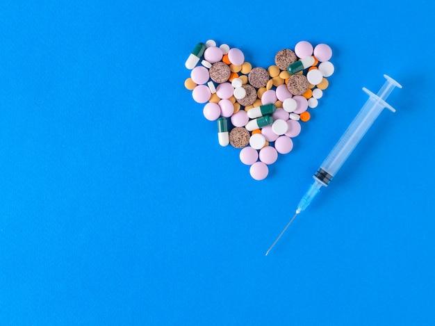 Herz der farbigen pillen und der spritze auf blauem hintergrund. der blick von oben. das konzept der behandlung und prävention von krankheiten. flach liegen.