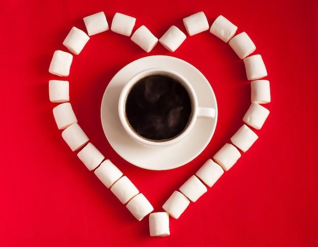 Herz des marshmallows und einer tasse kaffee auf rotem textilhintergrund. valentinstag