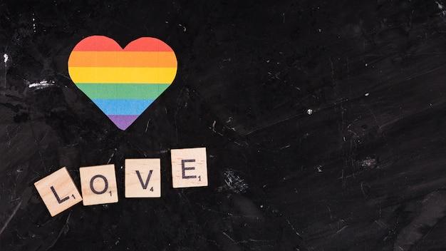 Herz des regenbogen-lgbt mit liebe unterzeichnen auf schwarzem raumhintergrund