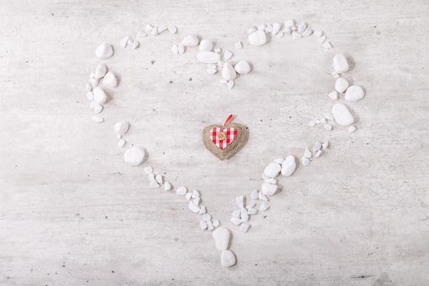Herz des valentinstags verziert mit weißen felsen über hellem hölzernem hintergrund. draufsicht, flach liegen. speicherplatz kopieren