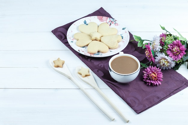 Herz-förmige kekse der hohen winkelansicht, tasse kaffee auf lila tischset mit blumen