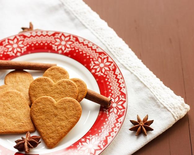 Herz-förmige plätzchen des lebkuchen mit zimtstangen und anis spielt auf einer roten platte die hauptrolle
