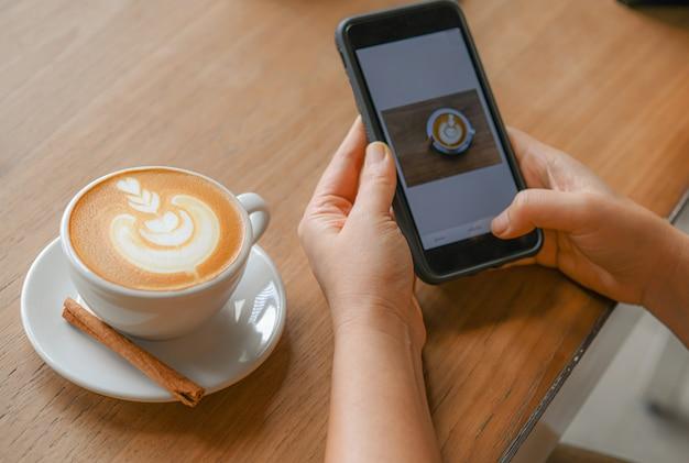 Herz-förmiger lattekaffee auf einem holztisch und leuten bereiten kaffeebilder im handy zu.