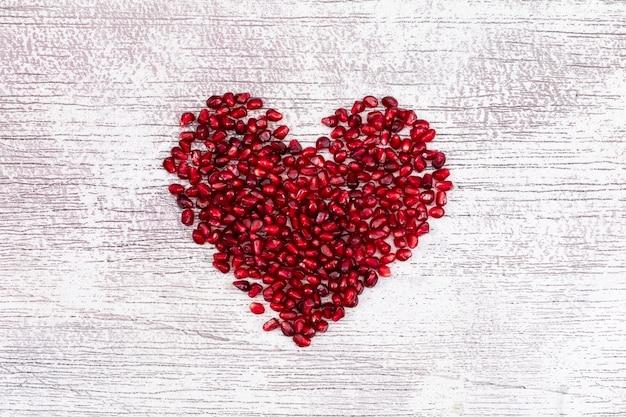 Herz formte draufsicht des granatapfels über weiße d-tabelle