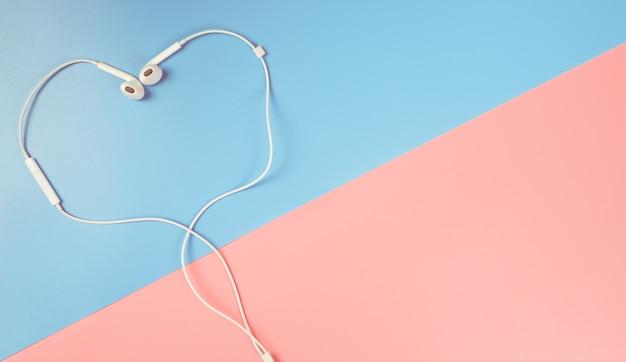 Herz formte kopfhörer auf blauem und rosa kopienraum
