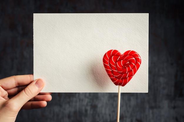 Herz formte lutscher mit weißem leerem blatt in der frauenhand auf einem dunklen hintergrund. modell zum valentinstag