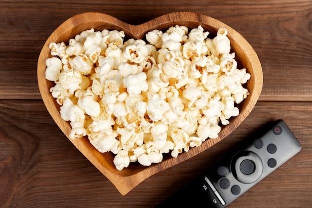 Herz formte popcorn in einer hölzernen schüssel und in einer fernsehfernbedienung auf einem holztisch