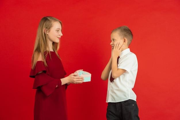 Herz geben. valentinstagfeier, glückliche, niedliche kaukasische kinder lokalisiert auf rotem studiohintergrund. konzept der menschlichen gefühle, gesichtsausdruck, liebe, beziehungen, romantische feiertage.