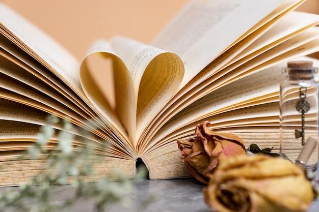 Herz geformt von der alten buchseite mit trockenen braunen rosen im weinlesefarbton