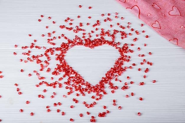 Herz geformt von granatapfelkernen auf weißem tisch