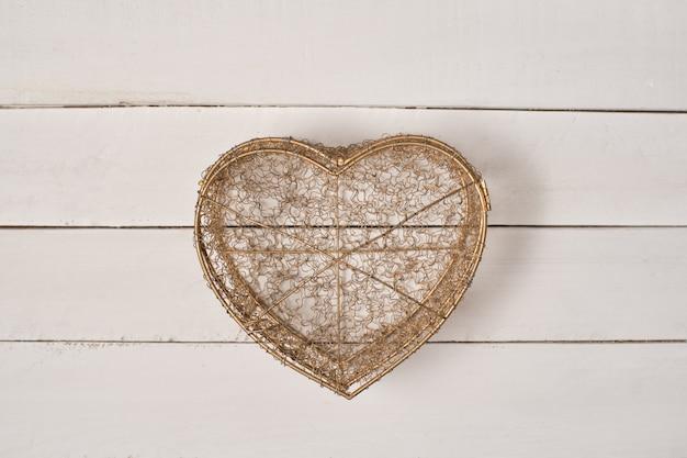 Herz geformte metalltransparenzbox auf weißem holztisch
