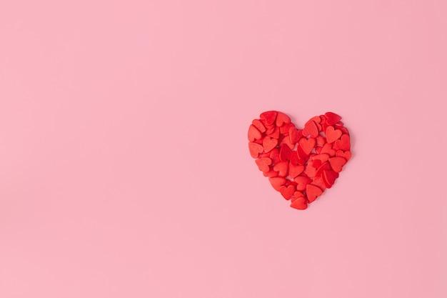 Herz gefüttert mit kleinen roten herzen auf rosa hintergrund. flache lage, kopierraum.