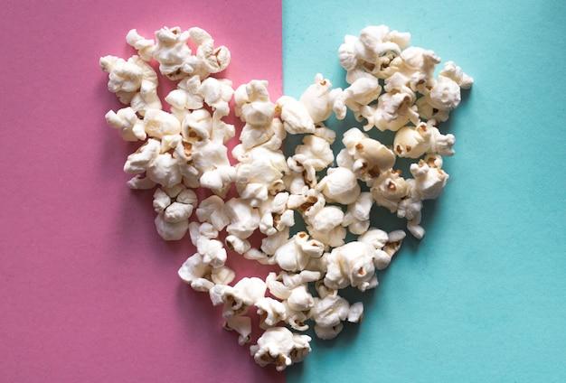 Herz gemacht vom köstlichen popcorn auf rosa pastell und blauem pastellfarbhintergrund