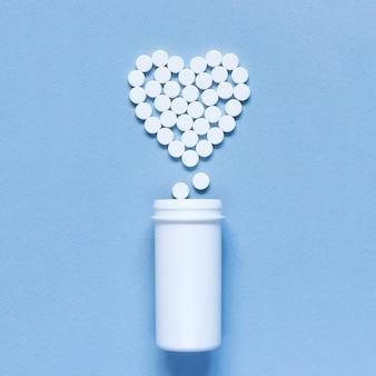 Herz gemacht von den pillen auf dem blauen strukturierten hintergrund