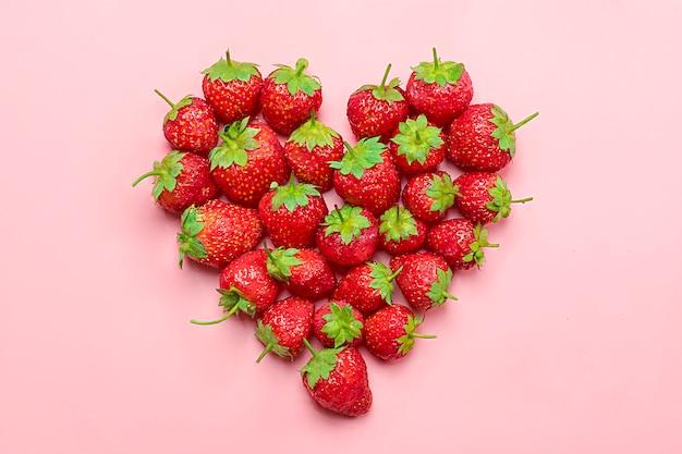 Herz gemacht von der deluxen, natürlichen saftigen erdbeere auf tendenzrosahintergrund