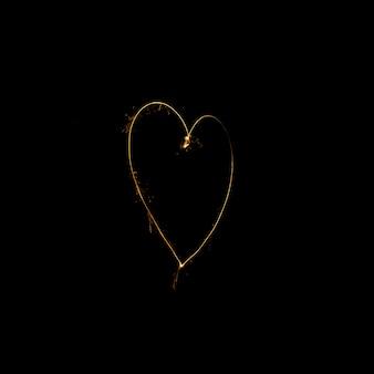 Herz gemacht von der wunderkerze auf schwarzem hintergrund