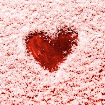 Herz gemalt auf der schneebedeckten windschutzscheibe eines autos.