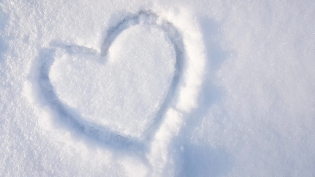 Herz gezeichnet auf dem schnee im park. liebe winter