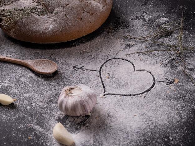 Herz gezeichnet auf mehl auf einem grauen tisch nahe hausgemachtem knoblauchbrot und gewürzen.