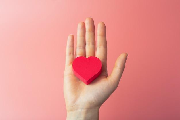 Herz in den händen einer frau auf einem farbigen hintergrund. hintergrund für valentinstag (14. februar) und liebe.