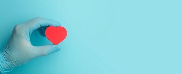 Herz in den händen eines arztes auf einem farbigen bannerhintergrund spendenwohltätigkeitsgesundheitsbehandlungshilfe...