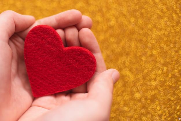 Herz in den palmen auf einem goldenen glänzenden hintergrund. valentinstag