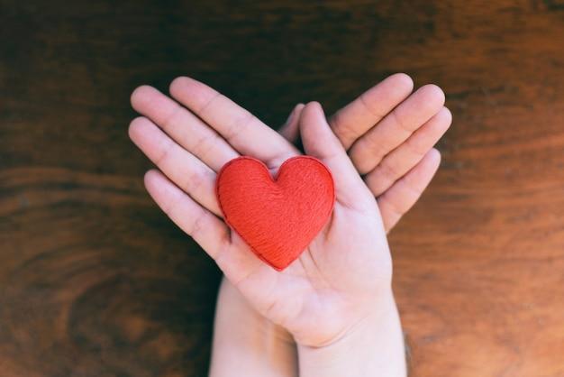 Herz in der hand für philanthropiekonzept - die frau, die rotes herz auf händen für valentinstag hält oder spenden, helfen, liebeswärme zu geben, mach s gut mit hölzernem hintergrund