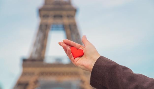 Herz in händen nahe dem eiffelturm in paris. selektiver fokus.