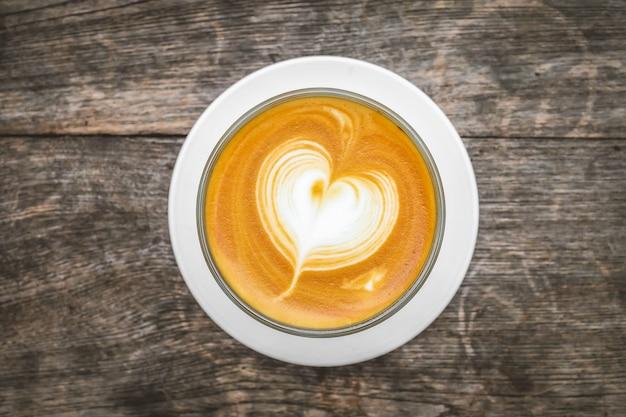 Herz-kaffeetasse und kaffeebohnen auf holzoberfläche. ansicht von oben.