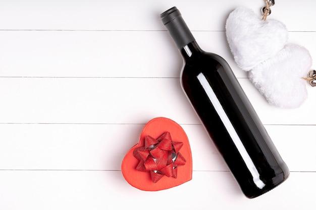 Herz, kerze, weinflasche auf weißer holzoberfläche. valentinstag konzept. flach liegen