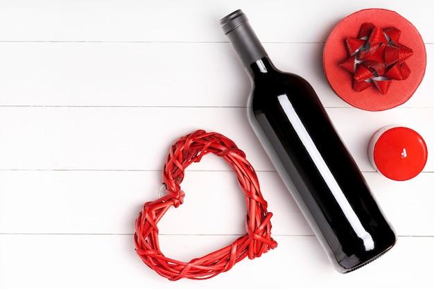 Herz, kerze, weinflasche auf weißer holzoberfläche. valentinstag konzept. flache lage, draufsicht, von oben, kopierraum