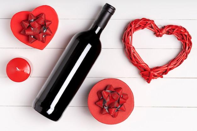Herz, kerze, weinflasche auf weißer holzoberfläche. valentinstag konzept. flache lage, draufsicht von oben