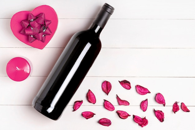 Herz, kerze, weinflasche, blumen auf weißer holzoberfläche. valentinstag konzept. flache lage, draufsicht