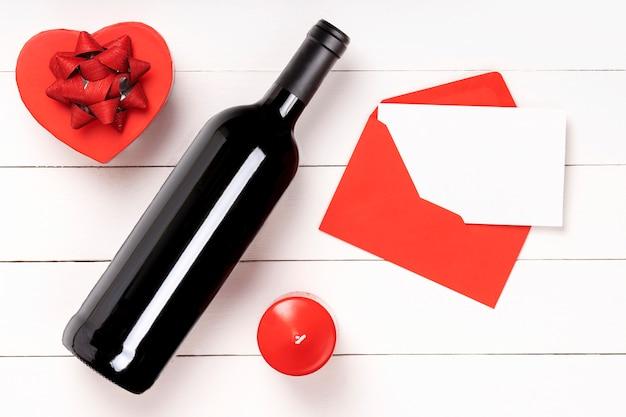 Herz, kerze, weinflasche, umschlag mit brief auf weißer holzoberfläche. valentinstag konzept. flache lage, draufsicht von oben