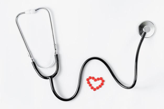 Herz-kreislauf-system. stethoskop und rote pillen in einer herzform auf weißer wand. speicherplatz kopieren. draufsicht