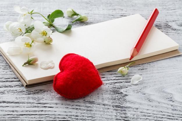 Herz mit blütenapfel auf weißer wand. spase kopieren